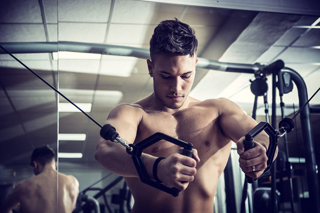 Young man training on gym equipment, pulling handle on cables. Source: theartofphoto - Fotolia (refer to: Training programme)
